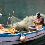 a fisherman sewing a net